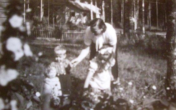 Salme  lasten kanssa pihalla  50-luvun alkupuolella. Takana mäellä Puustelli.