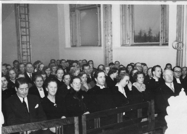 Kirkon 25-vuotisjuhlien päiväjuhlassa yhtiön teknillinen johtaja Väinö Huida on yksin etupenkissä. Toisella rivillä mm Hannikainen, silloinen väliaikainen pastori Lappalainen ja tuleva kirkkoherra Nuottamo vaimoineen.
